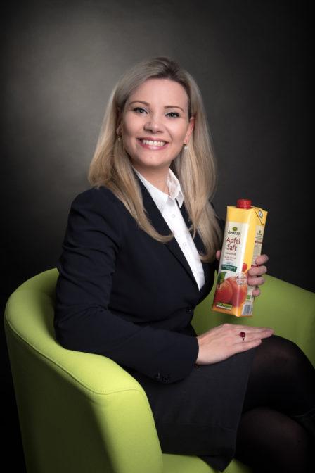 businessfoto melanie kollmann-alnatura gmbh, auf grünem stuhl mit apfelsaftpackung