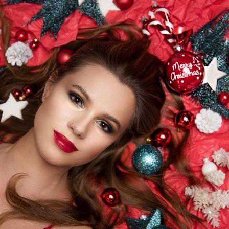 wunderschöne Frau mit langem dunkeln Haar und roten Lippen liegt in rotem Geschenkpapier und Christbaumschmuck