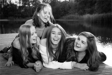 vier mädchen liegen am steg eines Teiches und lachen ausgelassen