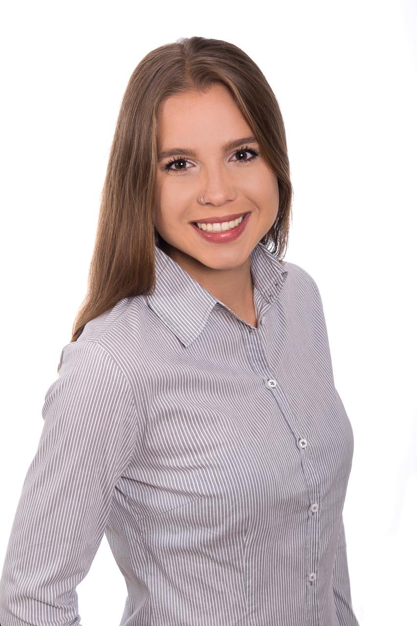 Bewerbungsfoto - Zu sehen ist eine junge frau mit langen dunklen haaren in einer schichten büro-look bluse
