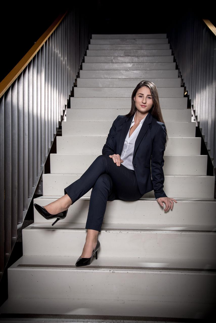 businessfoto einer jungen frau sie sitzt entspannt auf den Stiegen eines bürohauses und lächelt in die kamera