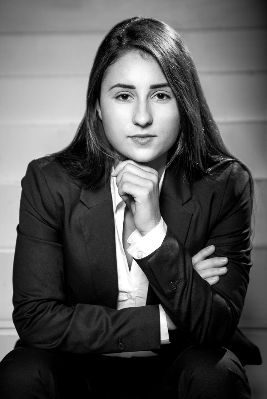 businessfoto einer jungen frau in schwarz weiß sie stützt sich auf ihren knien ab eine hand auf gestellt in denkerpose sie schaut ernst