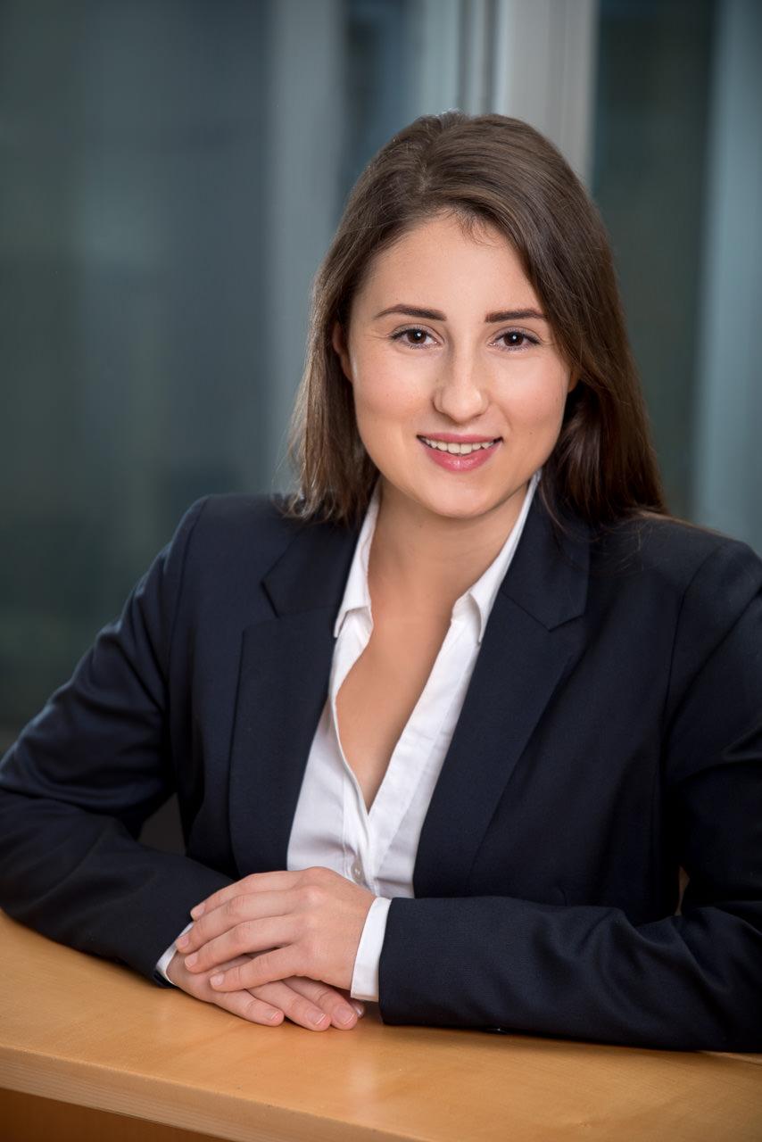 businessfoto einer jungen frau sie lehnt an einem holzpult im hintergrund sind glasflächen zu sehen sie lächelt