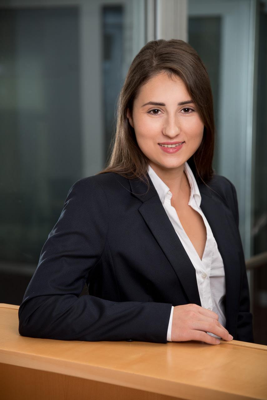 businessfoto einer jungen frau sie lehnt an einem holzpult sie steht seitlich gedreht im hintergrund sind glasflächen zu sehen sie lächelt