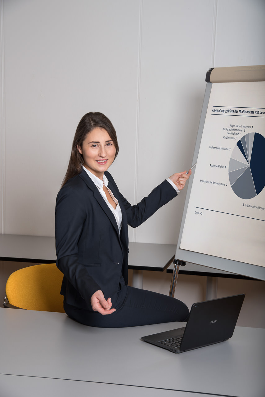 business foto einer jungen dunkelhaarigen frau. Sie sitzt am bürotisch bei ihrem aufgeklappten laptop