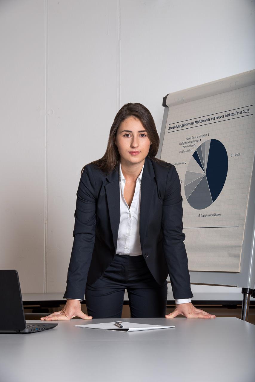 businessfoto einer jungen frau, sie lehnt am bürotisch und blickt direkt in die kamera