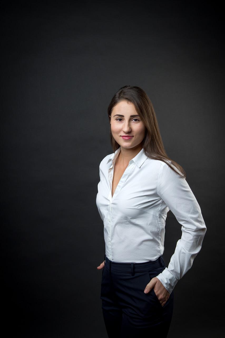 businessfoto einer jungen frau auf schwarzem hintergrund, sie steht, hat die hände entspannt in den hosentascehn und lächelt