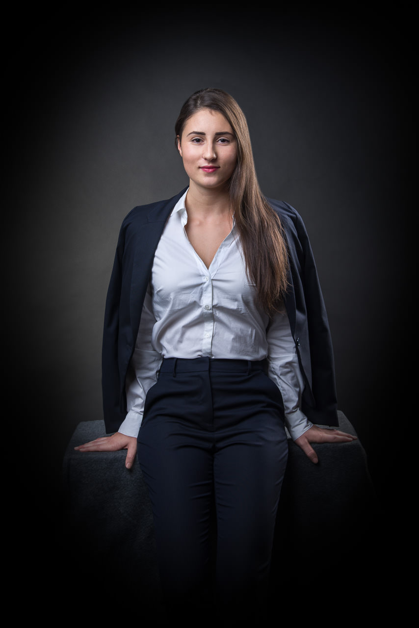 businessfoto einer jungen dunkelhaarigen frau, sie sitzt frontal hat ihren blazer um die schultern gehängt, das licht kommt von schräg oben