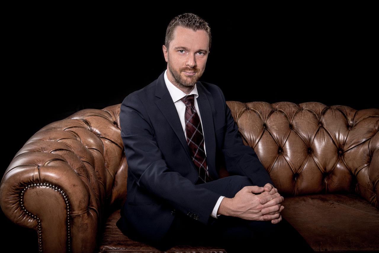 businessfoto eines mannes mittleren alters er sitzt auf einer braunen chesterfield couch und schaut ernst aber entspannt in die Kamera