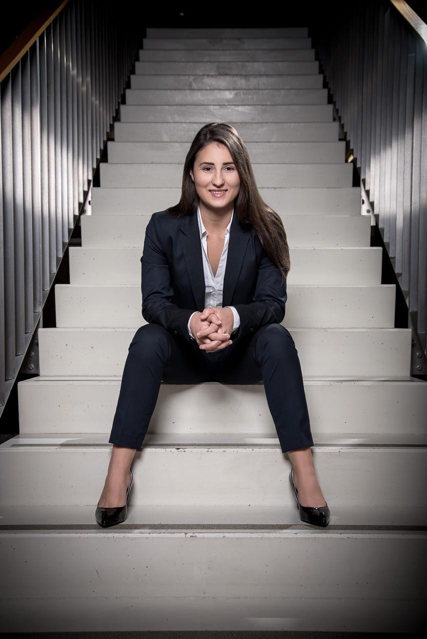 businessfoto einer jungen frau sie sitzt auf den stiegen eines bürohauses sie blickt frontal leicht von unten fotografiert in die kamera sie lacht
