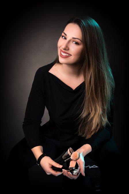 Visagistin sitzt auf ihrem Werkzeugkoffer auf schwarzem Hintergrund mit blauem Haarlicht