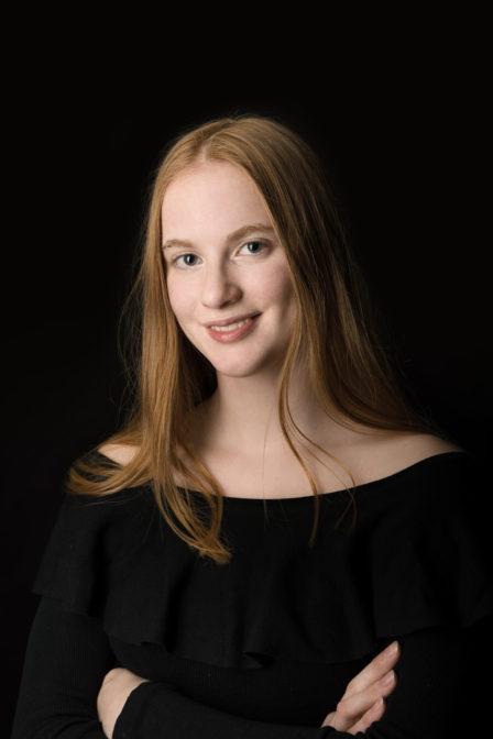 junge rothaarige dame portrait lächelnd auf schwarzem hintergrund