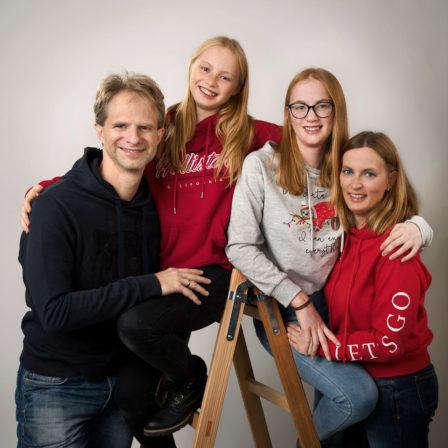 familie mit bunten pullis auf leiter