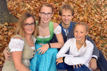familienfoto mit mutter vater und zwei schwestern alle in tracht sie sitzen im herbstlichen laub eng zusammen und lachen