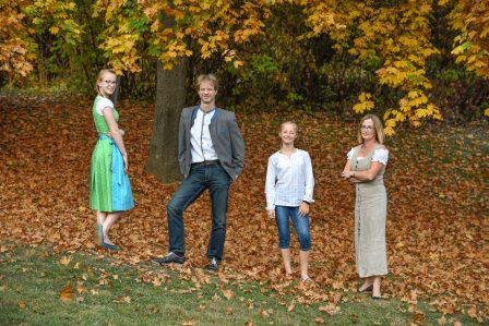 familienfoto mit mutter vater und zwei schwestern in tracht, sie stehen unter einem herbstlich verfärbten laubbaum und posen fröhlich