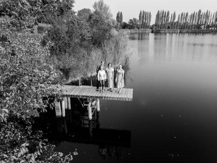 familienfoto aus der vogelperspektive mit einer drohne aufgenommen, die familie steht am steg des windradlteiches das foto ist in schwarz weiß gehalten