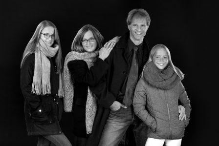 familienfoto in schwarz weiß die familie trägt winterkleidung sie stehen aneinandergelehnt der hintergrund ist schwarz