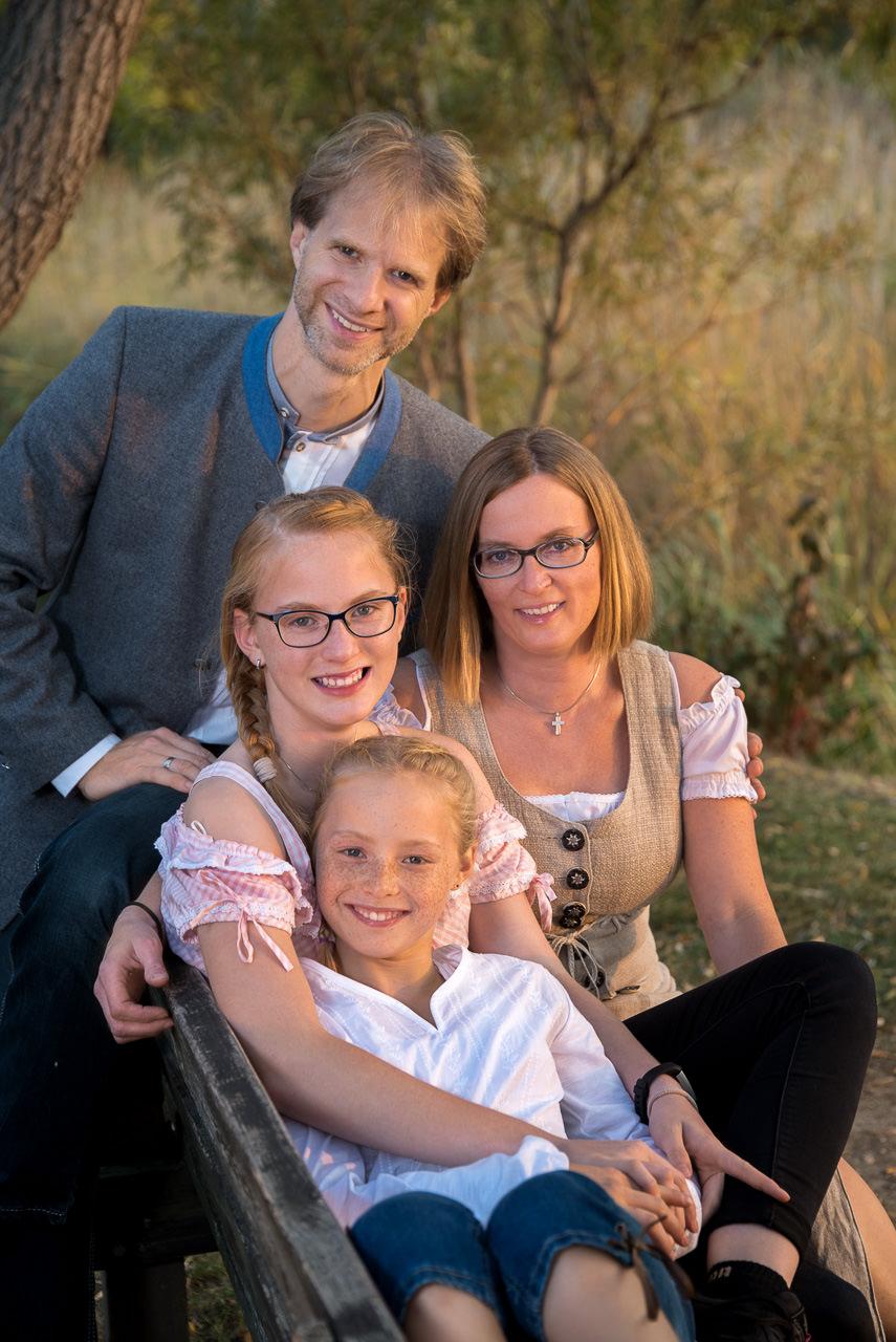 familenfoto bei sonnenuntergang die familie sitzt auf einer parkbank alle kuscheln miteinander im hintergrund eine weide