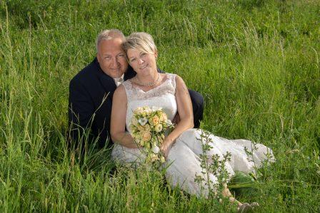 hochzeitsfoto das brautpaar sitzt aneinandergelehnt im grünen gras