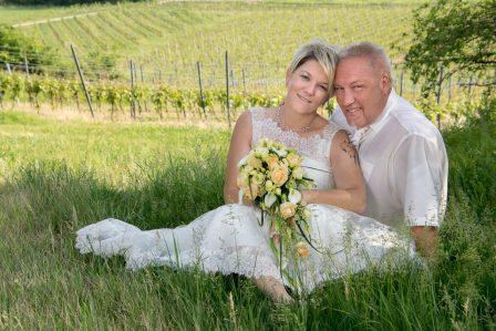 hochzeitsfoto brautpaar sitzt in der wiese im hintergrund die grünen weingärten