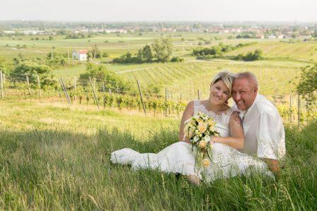 hochzeitsfoto brautpaar sitzt auf der weinbergkuppe im hintergrund der nächstgelegene ort