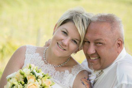 hochzeitsfoto brautpaar hat die köpfe zusammengekuschelt und lächelt in die kamera