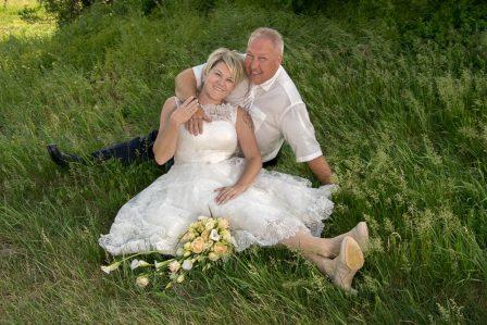 hochzeitsfoto das brautpaar sitzt lachend in der wiese