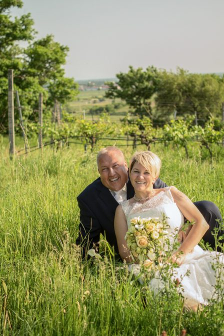 Hocheitsfoto das brautpaar sitzt lachend im hohen gras im hintergrund traiskirchens weingärten