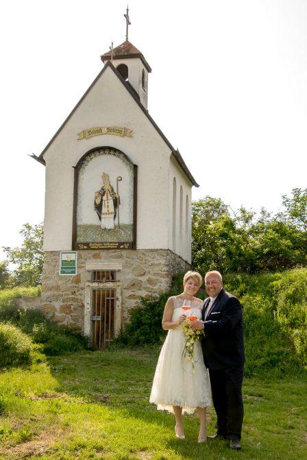 hochzeitsfoto das brautpaar steht vor der urbanuskapelle in traiskirchen und hält weingläser in der hand