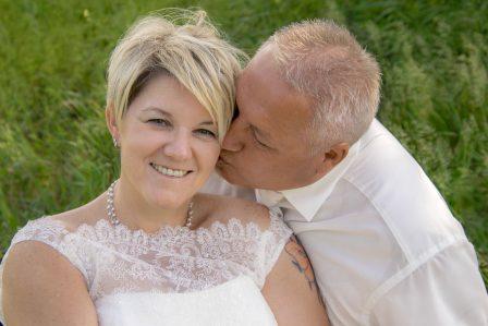 hochzeitsfoto der bräutigam gibt der braut einen kuss auf die wange