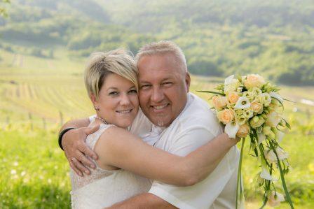 hochzeitsfoto brautpaar umarmt sich und blickt in kamera