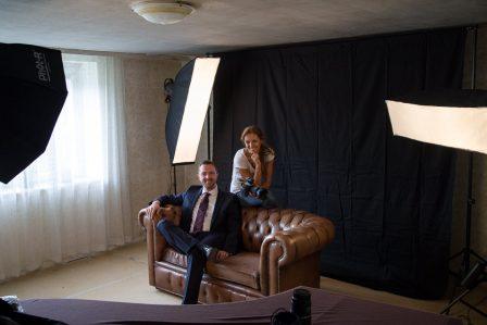 businessfoto mann im blauen anzug sitzt auf chesterfieldcouch
