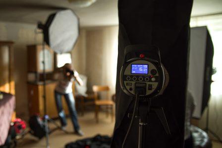 making of aufnahme wohnzimmer mit studiolampen und fotografin bei der arbeit
