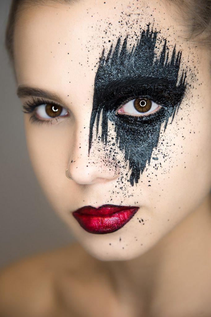 Frauenportrait mit roten lippen und effektvoll bemaltem gesicht