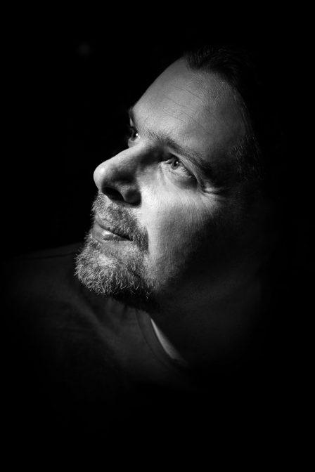 eindrucksvolles schwarz weiß foto von mann der ins licht blickt