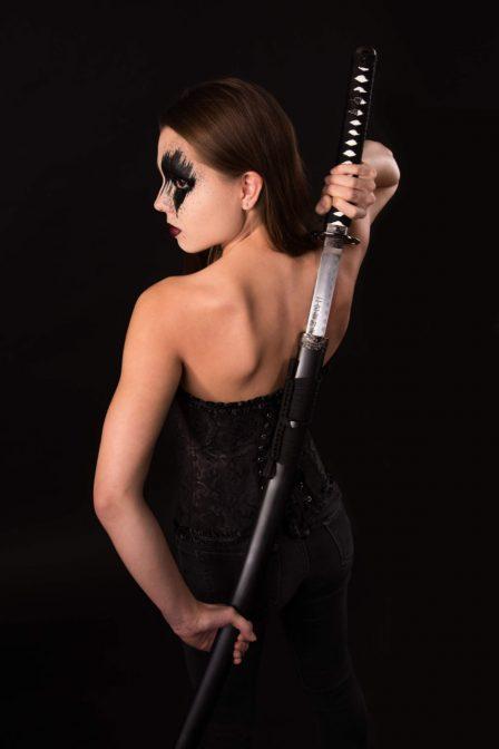 junge frau mit schwarz umrandetem auge hält samurei schwert in den händen