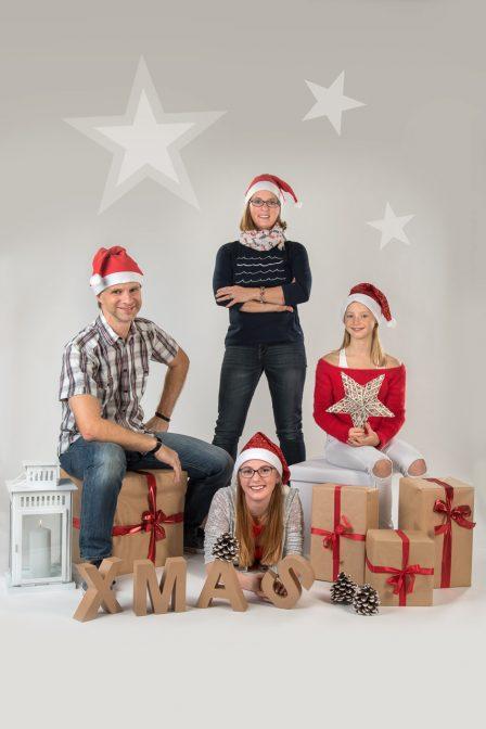 weihnachtsfamilienfoto im studio auf weißem hintergrund mit weihnachtsdeko alle tragen rote zipfelmützen