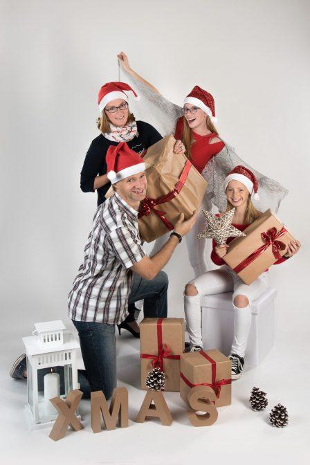 fröhliches weihnachtsfamilienfoto im studio auf weißem hintergrund mit weihnachtsdeko alle tragen rote zipfelmützen der vater bietet seiner tochter knieend ein pakerl an