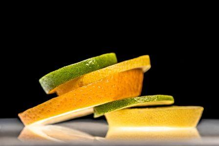 zitronen orangen und limetten scheiben gestapelt und effektvoll beleuchtet