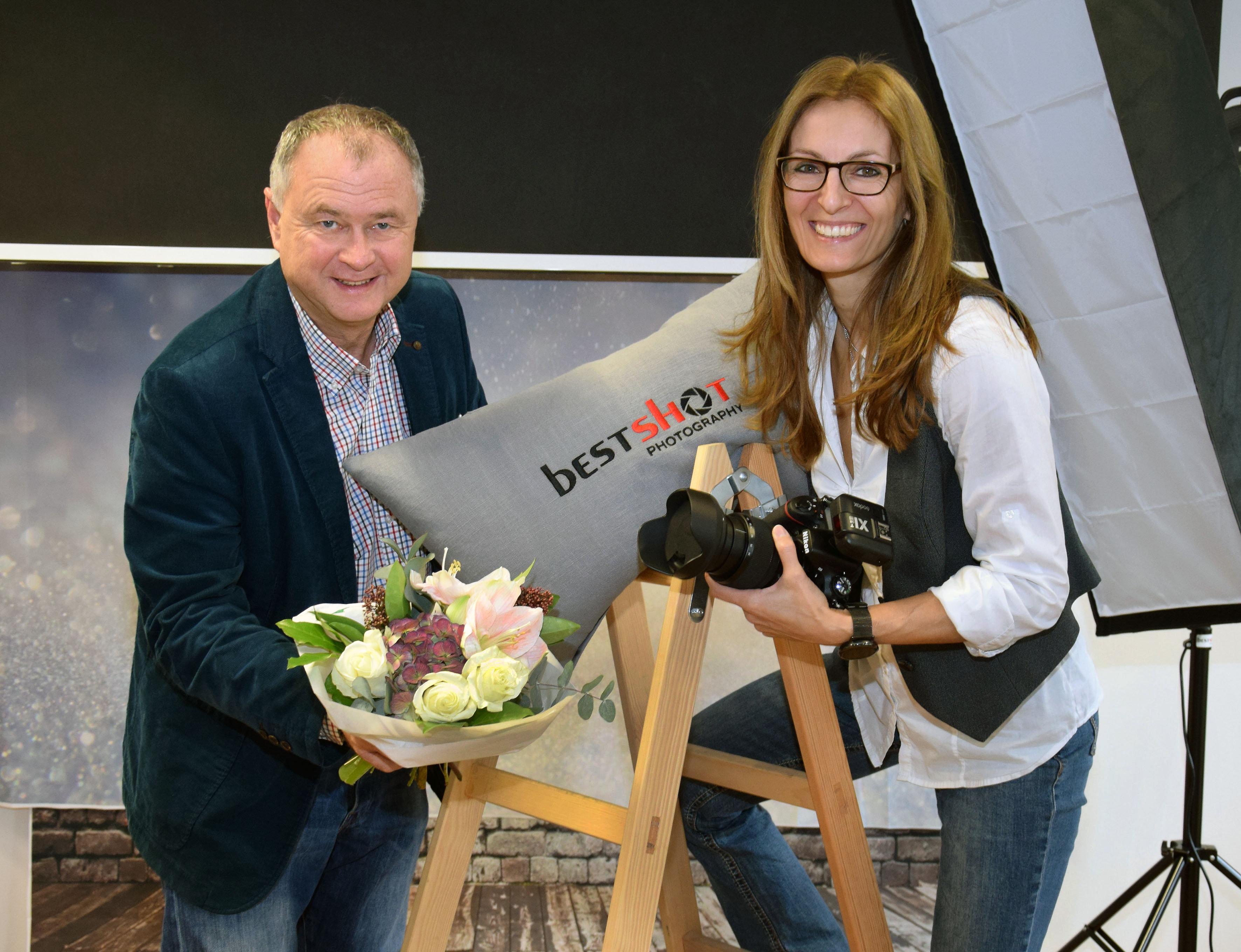 Der mödlinger Bürgermeister Hans Stefan Hintner mit Blumenstrauß und Meisterfotografin Raphaela Tod im Fotostudio