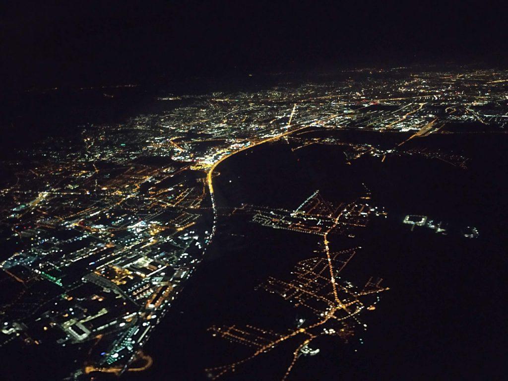 luftaufnahme nachts, zu sehen sind beleuchtete Straßen und Städte