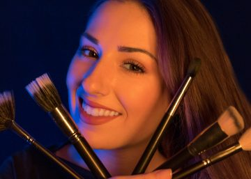Junge Frau mit langen braunen Haaren mit Visagistenpinseln - blau/orange beleuchtet