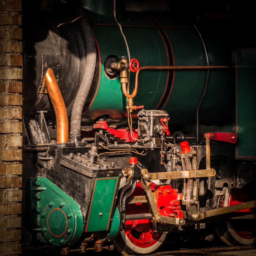 Ausschnittfoto einer grün-roten Dampflok in der Wagenhalle