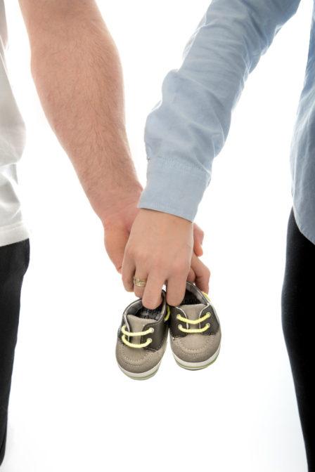 paar hält babyschuhe babybauchshooting